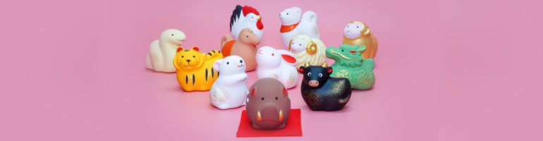 Cute small figurines of each Chinese zodiac animal sit on a pink background. From left to right: Snake, tiger, horse, rat, chicken, rabbit, pig, sheep, dog, ox, dragon, and money.