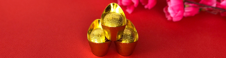 Three gold pendants are towered in a triangle on a red background with cherry blossoms in the background. This represents the trines in the Chinese zodiac.